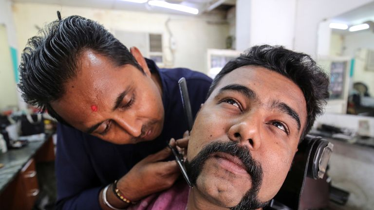 A man getting an 'Abhinandan' at a barbershop in Ahmedabad