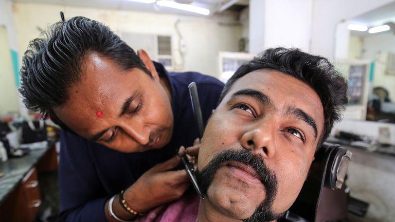 A man getting an 'Abhinandan' at a barbershop in Ahmedabad