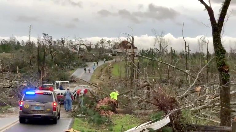 People clear fallen trees and debris on a road following the tornado in Alabama