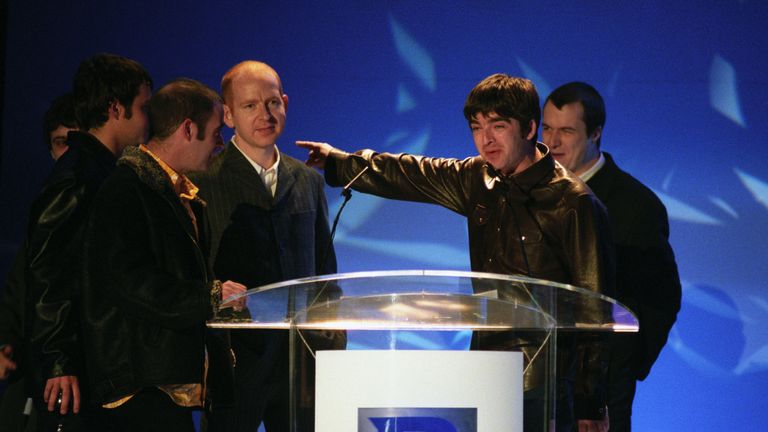 Alan McGee on stage with Oasis at the Brit Awards in 1996