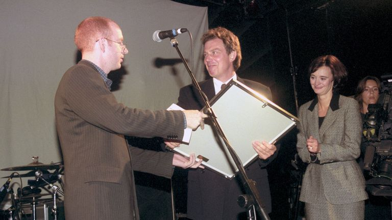 Cherie Booth looks on as Tony Blair receives a platinum disc of Oasis album What's The Story, Morning Glory from Alan McGee of Creation Records in Blackpool 1996