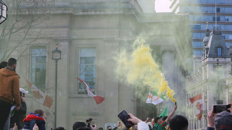 People set off flares in the protests in Trafalgar Square on Saturday