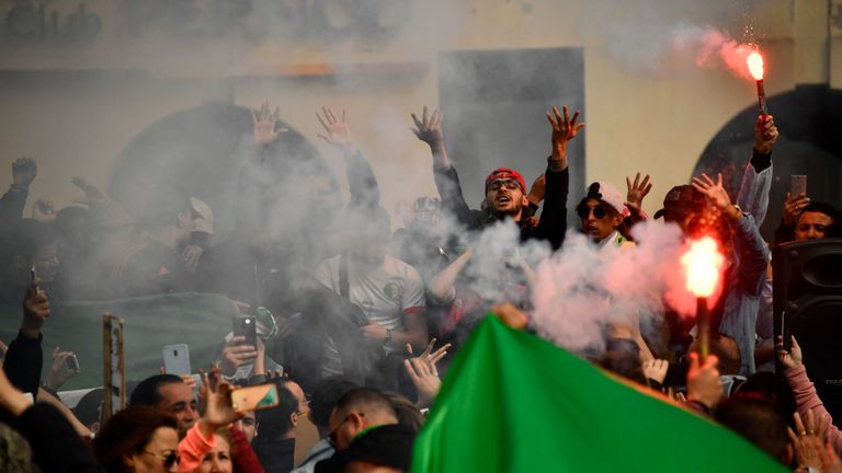 Demonstrators wave an Algerian flag and red flares during a protest over fears of plot to prolong the Algerian president's rule