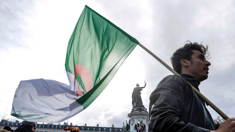 A demonstrator holds an Algerian flag during a protest over fears of plot to prolong the Algerian president's rule