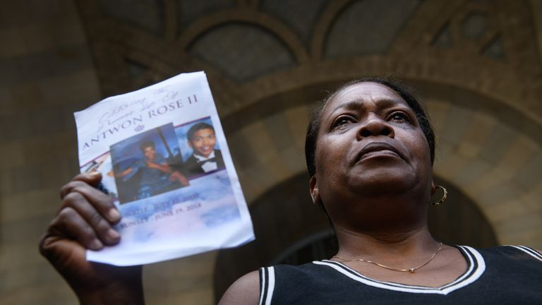 Carmen Ashley, the great aunt of Antwon Rose II holds the memorial card from his funeral during a protest