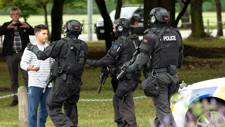 AOS (Armed Offenders Squad) push back members of the public following a shooting