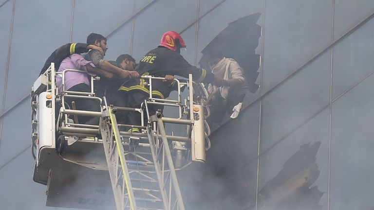 Bangladeshi firefighters rescue someone from the burning tower