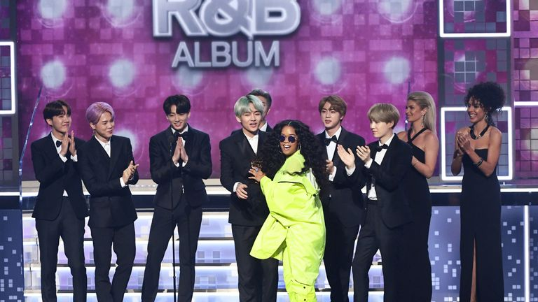 H.E.R. accepts and award from BTS at the Grammys
