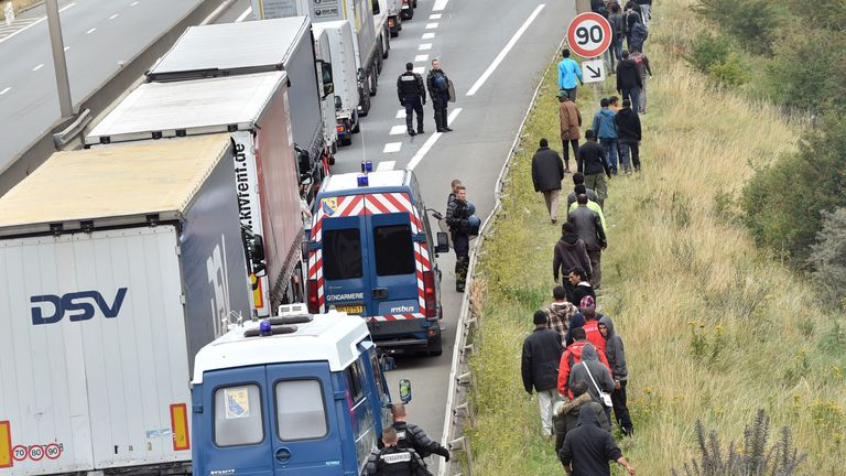 French riot police stand on the side of the road to prevent migrants from approaching lorries on the road leading to the ferry port in Calais, northern France, on August 5, 2015