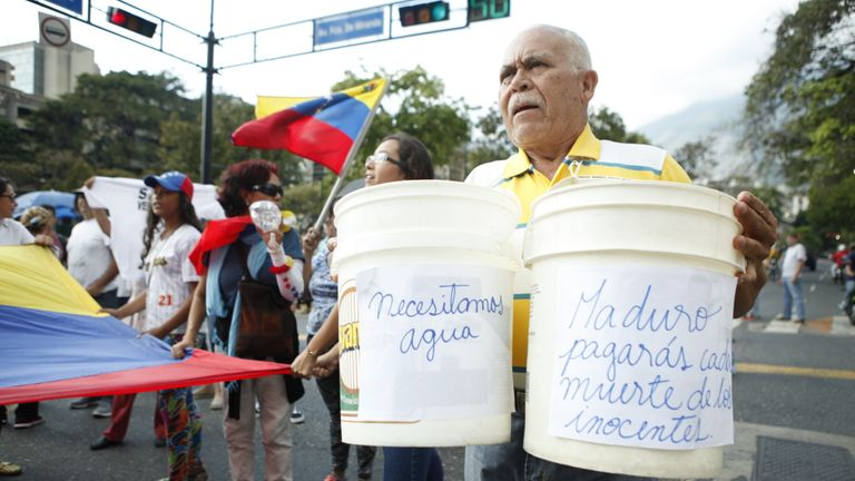 This man's signs say 'we need water' and on the right 'Maduro you will pay for the deaths of the innocents'