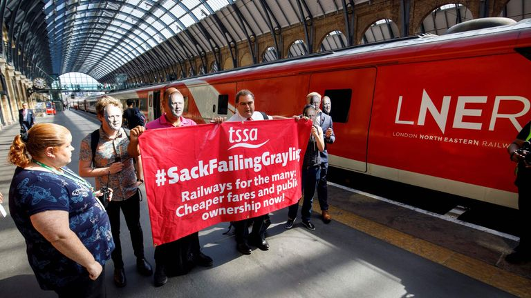 Demonstators holding masks sepicting Britain's Transport Secretary Chris Grayling protest at King's Cross rail station in London on June 25, 2018, during a photocall for the re-launch of the London North Eastern Railway (LNER) rail service on the East Coast mainline.