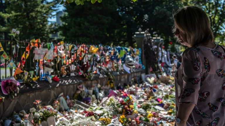 A woman views flowers and tributes by the wall of the botanic gardens on March 24, 2019 in Christchurch, New Zealand