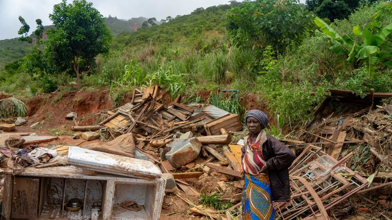 A woman stands next to her destroyed belongings in Chimanimani, Zimbabwe