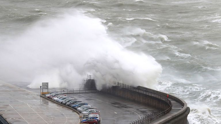 Waves crash onto the harbour in Dover
