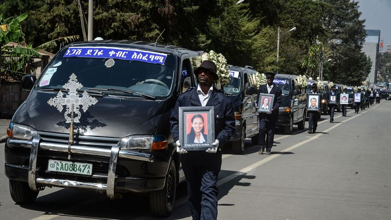 Mourners walk beside a procession of cars at a mass funeral