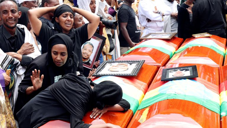 Women mourn next to the coffins of relatives who died in the Ethiopian Airlines crash
