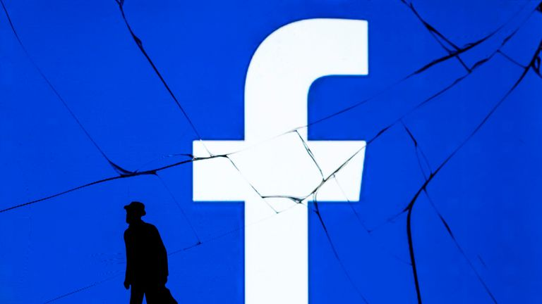 This photograph taken on May 16, 2018, shows a figurine standing in front of the logo of social network Facebook on a cracked screen of a smartphone in Paris