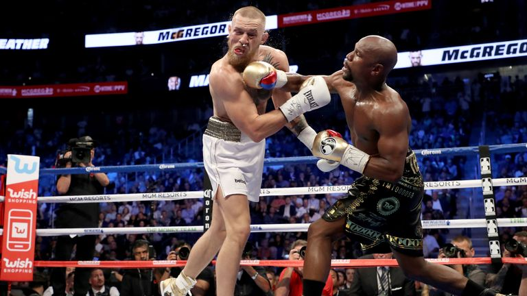 Floyd Mayweather Jr throws a punch at Conor McGregor during their super welterweight boxing match