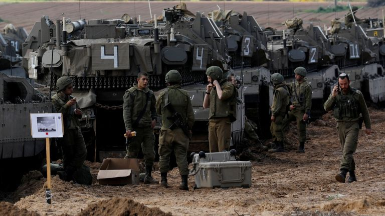 Israeli soldiers chat next to armoured personnel carrier's (APC) near the border with Gaza