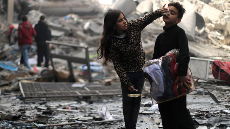 A Palestinian girl cleans the face of her brother outside their destroyed house after an Israeli missile strike