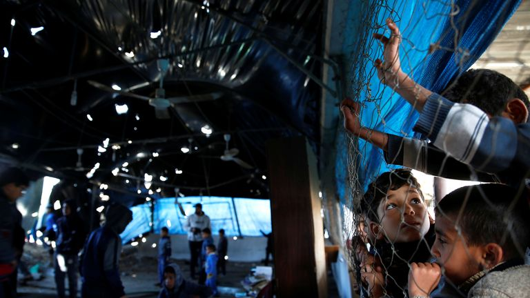 Boys peer through fencing as at a damaged mosque in Gaza