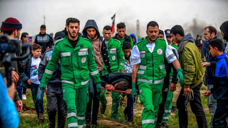 Paramedics carry a man away on a stretcher during the protests on the Gaza border