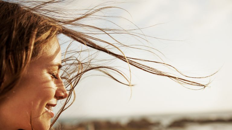 Cropped view of a young woman with the wind in her hair