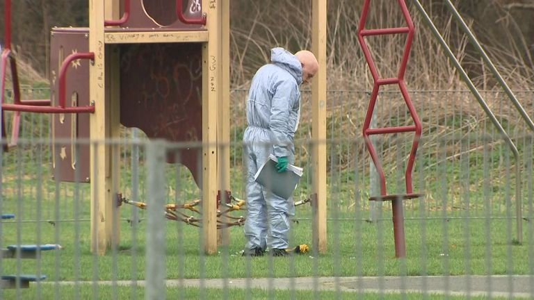 Forensic officers inspect the scene where a 17-year-old girl was stabbed to death