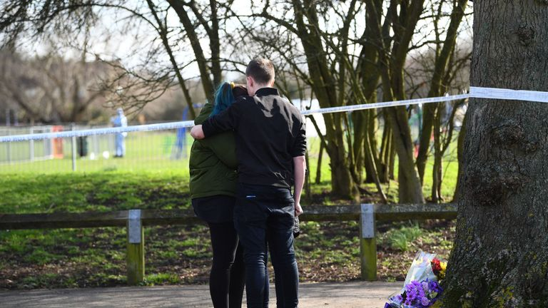 People place flowers near the scene of the stabbing