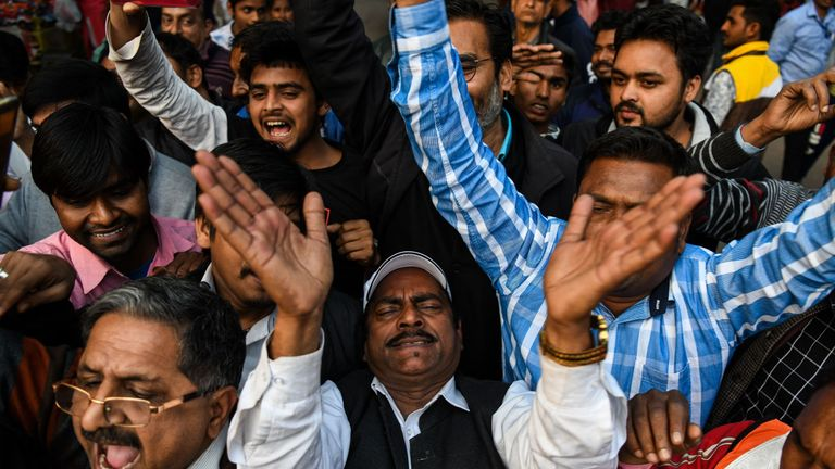 People celebrate in New Delhi as they await the pilot's return