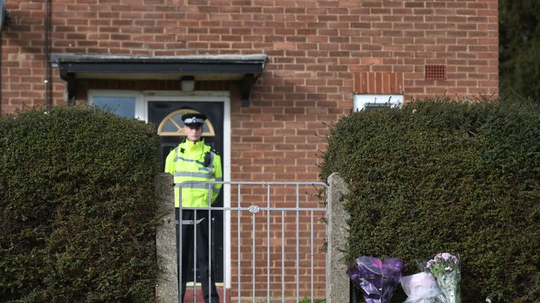 A police officer stands outside the house where the bodies were found