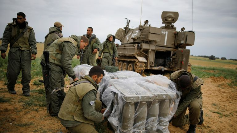 Israeli soldiers cover shells near the Gaza border