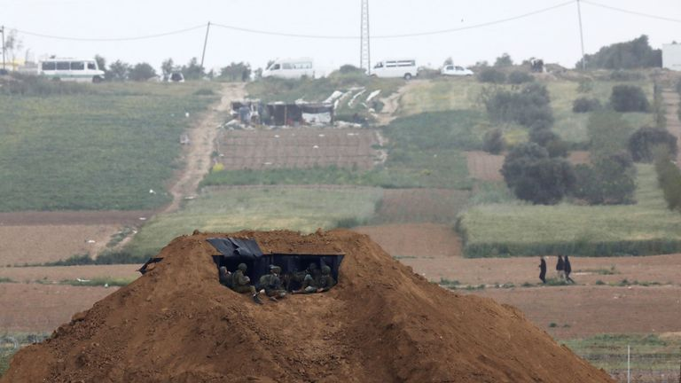 Israeli troops are positioned in an earth barrier in Nahal Oz