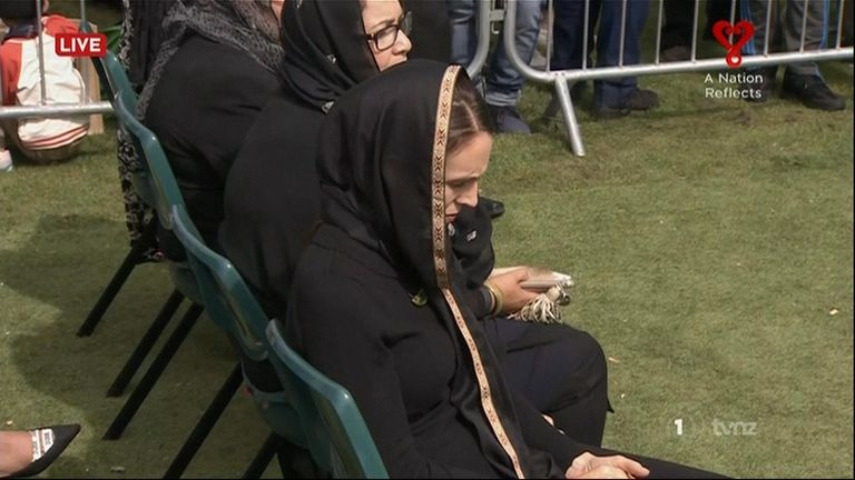 Jacinda Ardern bows her head as she listens to the speeches in the park