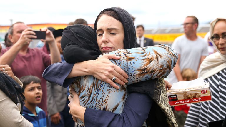 Jacinda Ardern embraces a woman outside a mosque