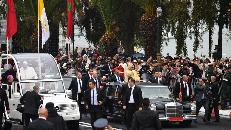 King Mohammed VI (R) waves to the crowd from his car as he arrives with Pope Francis (L) in his pope mobile in Tour Hassan square upon the pontiff's arrival in the North African country on March 30, 2019