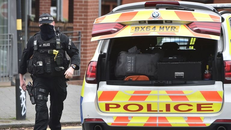 A firearms officer walks to his vehicle at the scene