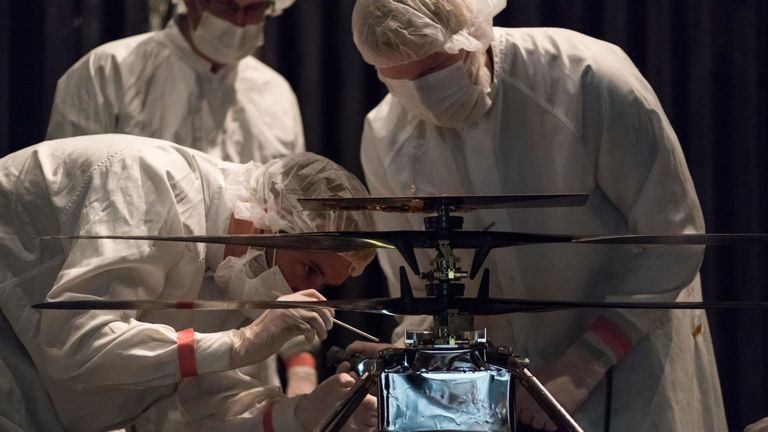 NASA's Mars Helicopter team attaching a thermal film enclosure to the fuselage of the flight model at NASA's Jet Propulsion Laboratory in Pasadena, California