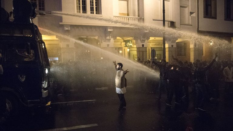 - A Moroccan protester raises his arms in front of water cannons used by the police during a demonstration in the capital Rabat on March 24, 2019. - The police dispersed during the night a gathering of teachers who reportedly attempted to camp in front of the parliament, demanding permanent contracts within the national education system.