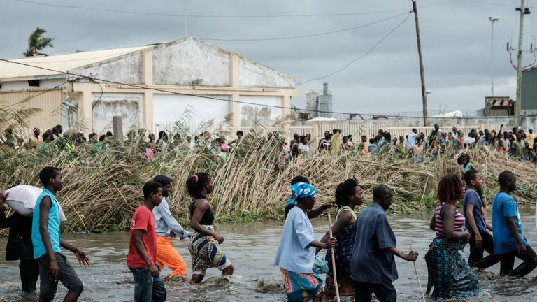 People try to loot rice sacks from a warehouse surrounded by water in Beira, Mozambique