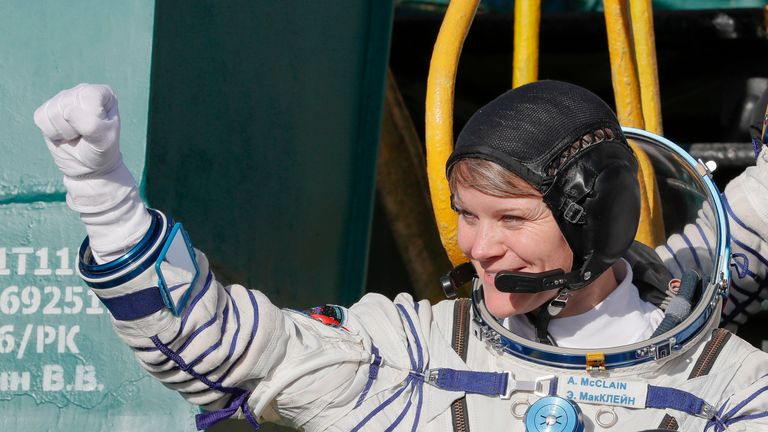 Anne McClain gestures as she boards the Soyuz MS-11 spacecraft