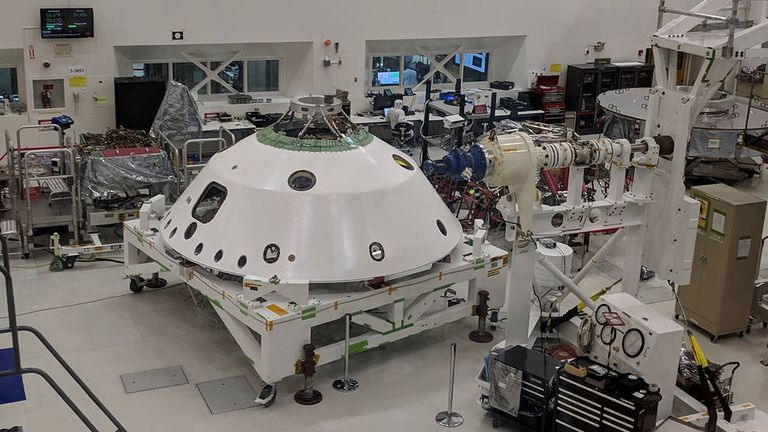 With the backshell that will help protect the Mars 2020 rover during its descent into the Martian atmosphere visible in the foreground, a technician on the project monitors the progress of Systems Test 1.