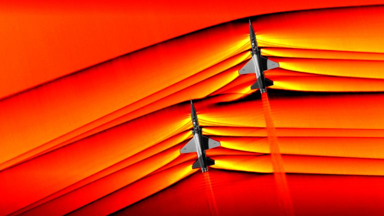 Using the schlieren photography technique, NASA was able to capture the first air-to-air images of the interaction of shockwaves from two supersonic aircraft flying in formation. These two U.S. Air Force Test Pilot School T-38 aircraft are flying in formation, approximately 30 feet apart, at supersonic speeds, or faster than the speed of sound, producing shockwaves that are typically heard on the ground as a sonic boom. The images, originally monochromatic and shown here as colorized composite i