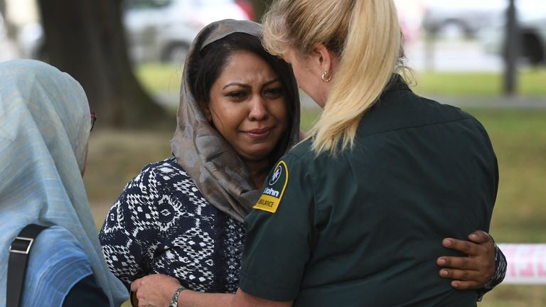A St John Ambulance comforts to a woman outside the al Noor mosque
