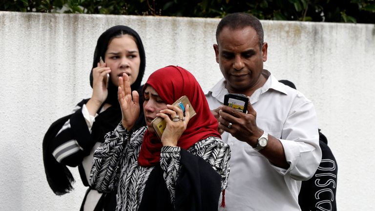 People wait outside a mosque in central Christchurch, New Zealand