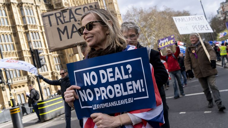Pro-Brexit protestors carry placards during a protest near the Houses of Parliament in London on March 13, 2019. - British MPs will vote Wednesday on whether the country should leave the EU without a deal in just over two weeks, after overwhelmingly rejecting a draft divorce agreement. The House of Commons is expected to vote against a 'no deal' Brexit, although this could still happen on March 29 unless it can agree on what should happen instead.