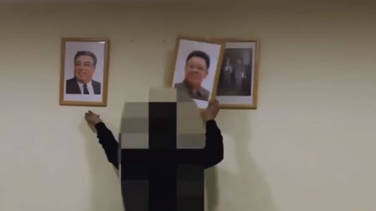 The intruders are seen removing portraits of North Korean leaders from the walls of the embassy...