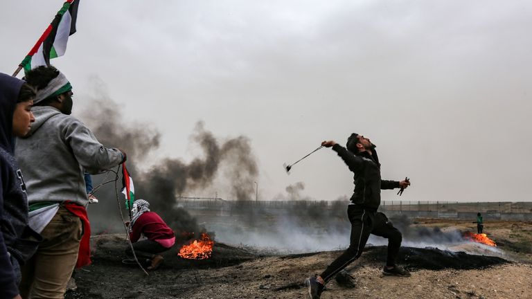 A Palestinian protester using a slingshot to target Israeli forces