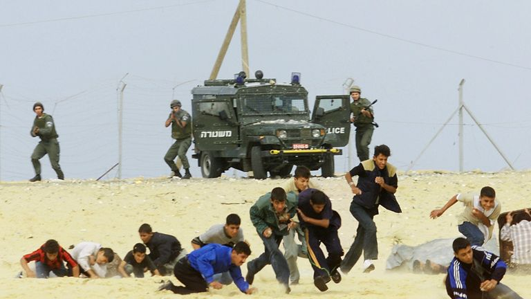 Israeli soldiers shoot at stone-throwing Palestinian teenagers in the Gaza Strip during clashes in October 2000