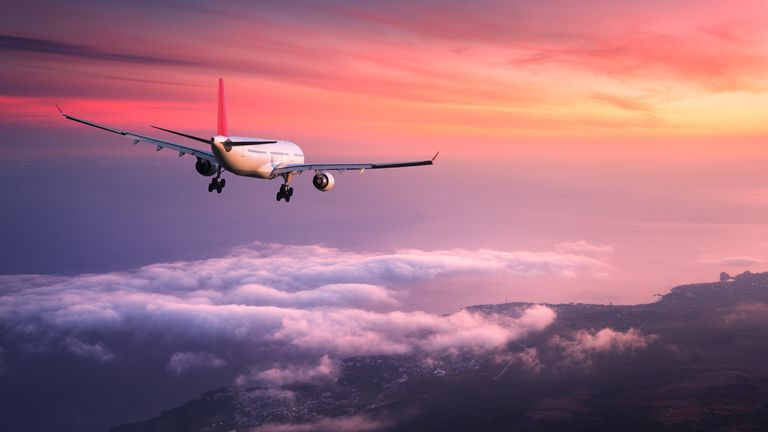 Airplane. Landscape with big white passenger airplane is flying in the red sky over the clouds at colorful sunset. Journey. Passenger airliner is landing at dusk. Business trip. Commercial plane (Airplane. Landscape with big white passenger airplane i